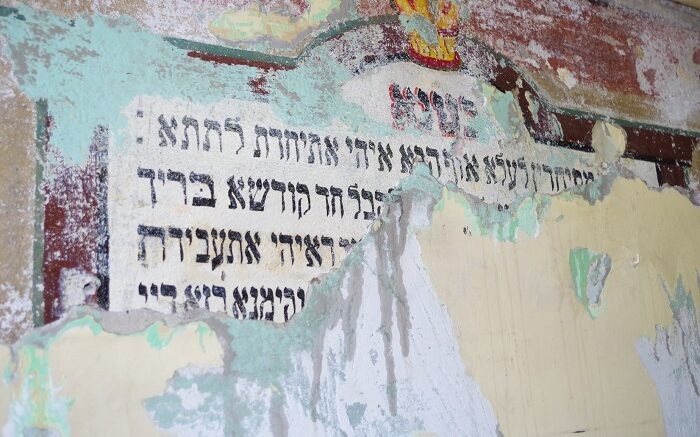 Fragment ściany z wyłaniającymi się spod farby napisami w języku hebrajskim